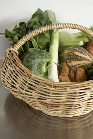 Winter produce, fresh vegetables in basket stock photo, Still life of vegetables on stainless steel bench in wicker basket by Gary Cookson