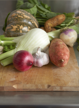 Raw produce - winter vegetables stock photo, Still life of winter vegetables on wooden chopping board. Stainless steel bench in background by Gary Cookson