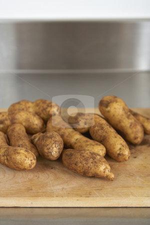 Fresh produce, potatoes stock photo, Wooden chopping board with fresh, dirty potatoes. Stainless steel bench in background. Shallow focus by Gary Cookson
