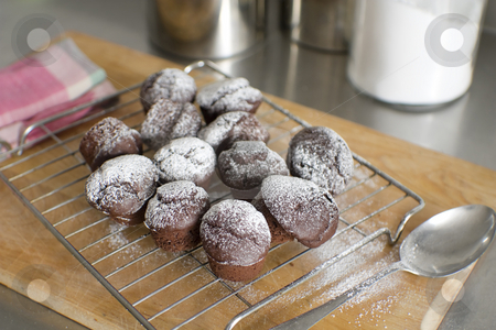 Freshly baked chocolate cupcakes stock photo, Chocolate cupcakes lightly dusted with sugar cool on a rack in modern kitchen by Gary Cookson