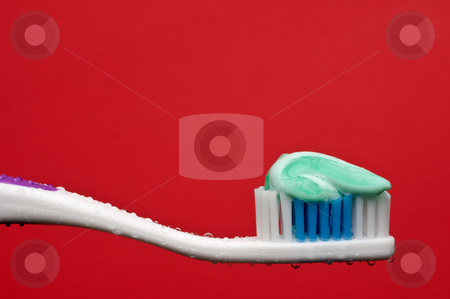 A horizontal closeup of a manual toothbrush with a glob of tooth stock photo, A horizontal closeup of a manual toothbrush with a glob of toothpaste and water droplets on a red background by Vince Clements
