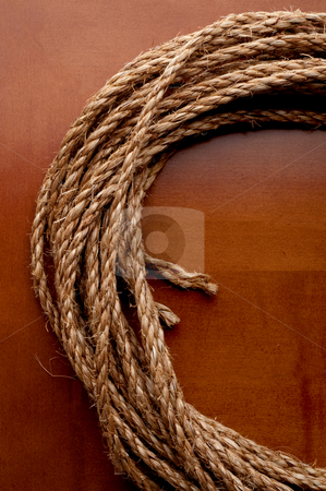 A vertical image of a coil of rope on a wooden surface stock photo, A vertical image of a coil of rope on a wooden surface by Vince Clements
