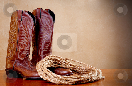 A horizontal image of a pair of brown cowboy boots and a coil of stock photo, A horizontal image of a pair of brown cowboy boots and a coil of rope on a wooded surface with an old textured background by Vince Clements
