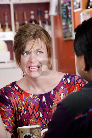 Appalled woman in coffee house with male friend stock photo, Appalled pretty woman with red hair in coffee house with male friend by Scott Griessel