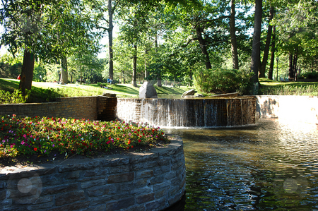 Pont in a park. stock photo, An big pond in a nice park in Montreal with a small waterfall and flower beds in bright sunshine, with shadow areas. by Horst Petzold
