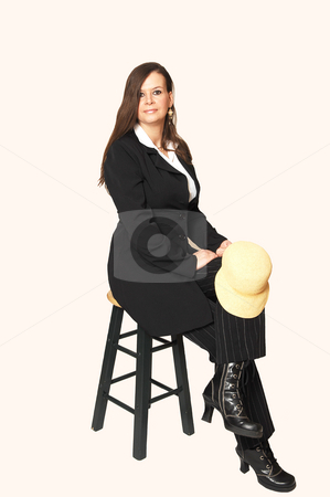 Woman sitting on bar chair. stock photo, Middle age woman in an black coat and boots sitting on a bar chair in the studio for light beige background, by Horst Petzold