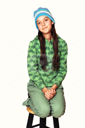 Teenager kneeling on chair. stock photo, Girl dressed all in green with long brown hair and blue cap kneeling on a bar chair for white background. by Horst Petzold