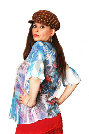 Woman with brown cap. stock photo, Middle age woman in a blue blouse and red skirt with an brown cap standing in the studio with long brown hair looking over her shoulder in the camera. For white background. by Horst Petzold