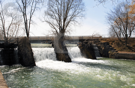 Water running over a weir. stock photo, A small river in the spring running over a weir after a heavy rainfall. by Horst Petzold