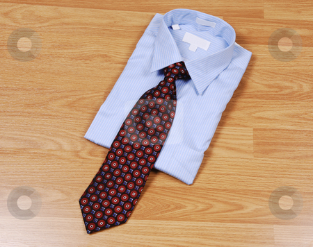 Blue dress shirt with tie. stock photo, A light blue dress shirt on a wood surface with an red and black tie for sale in the store. by Horst Petzold