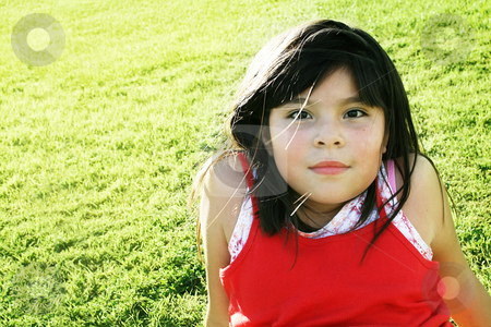 Girl relaxing in park stock photo, Cute mixed race girl sitting on grass with relaxed look by iodrakon