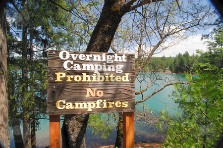 Camping Prohibited Sign stock photo, A no campfire and no camping wooden sign in frint of a scenic lake and forest by Lynn Bendickson