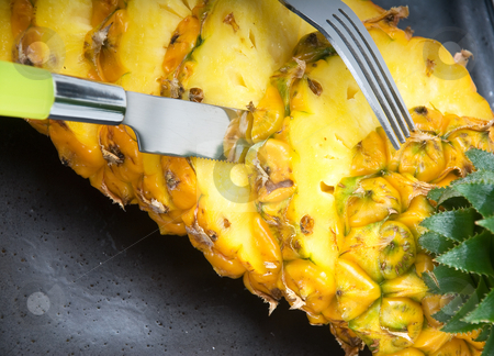 Pineapple stock photo, Ripe vivid pineapple sliced on a black plate with knife and fork by Francesco Perre