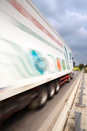 Blured track stock photo, Speeding transport car on a road with yellow fields in background by Juraj Kovacik