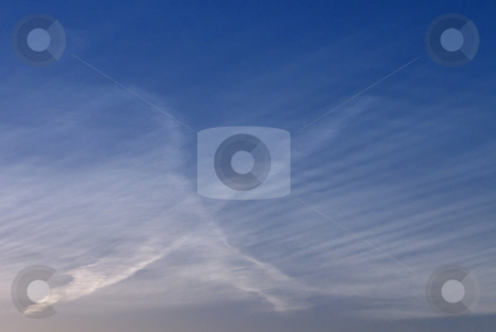Cursive X In The Sky stock photo, Condensation trails from jets cross in the sky to form an x. by Kathy Piper