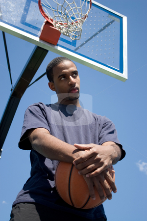 Basketball Player Thinking stock photo, Young African American man posing with a basketball underneath the backboard. by Todd Arena