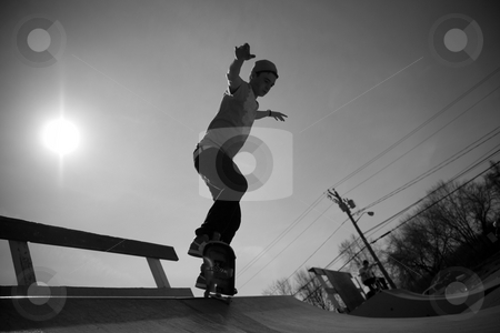 Skateboarder On The Ramp stock photo, Portrait of a young skateboarder skating on a ramp at the skate park. by Todd Arena