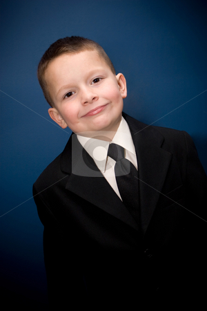 Happy Young Boy stock photo, Young boy wearing a suit smiling in front of a blue backdrop. by Todd Arena