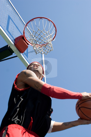 Basketball Player Dunking stock photo, A young basketball player under the rim going for a reverse slam dunk.  Shallow depth of field with stronger focus on the goal. by Todd Arena