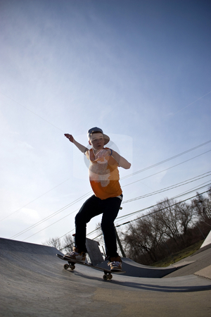 Skateboarder at the Skate Park stock photo, Portrait of a young skateboarder skating down a ramp at the skate park. by Todd Arena