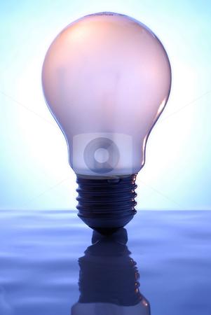 Light bulb stock photo, Light Bulb on blue, reflective surface. by Gjermund Alsos
