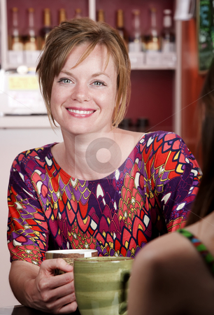 Woman in coffee house with female friend stock photo, Pretty woman with red hair in coffee house with female friend by Scott Griessel