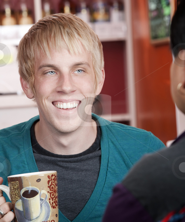 Man in coffee house with male friend stock photo, Handsome young man in coffee house with male friend by Scott Griessel