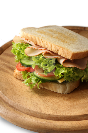 Delicious sandwich stock photo, Delicious sandwich with layers of pickle, salad, cheese, tomatoes and turkey ham. Shallow depth of focus. Focus is on the front of the sandwich. by Jan Martin Will