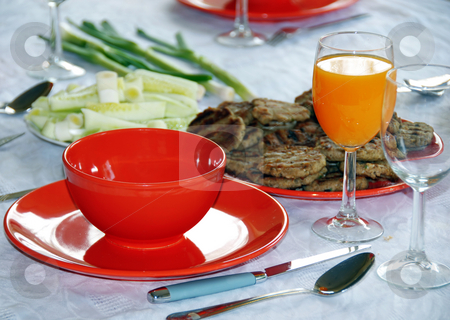 Dinner stock photo, Red plates and orange juice served on table in kitchen by Julija Sapic