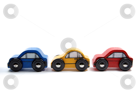 Three wooden toy cars in a row stock photo, Three simple wooden toy cars in a row, against a white background. by Gjermund Alsos