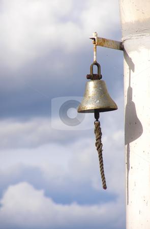 Ship's bell stock photo, Ferruginous ship bell on a background cloudy sky by Sergej Razvodovskij