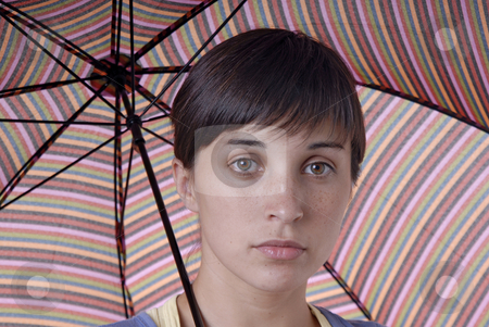 Woman with umbrella stock photo, Young brunette girl with umbrella in colors by Rui Vale de Sousa