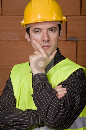 Pensive stock photo, Engineer with yellow hat with a brick wall as background by Rui Vale de Sousa