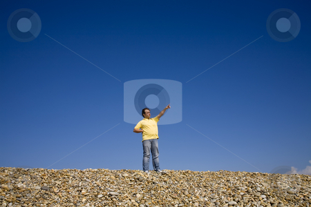 Man pointing at beach stock photo, Young man pointing at the beach with blue sky by Rui Vale de Sousa