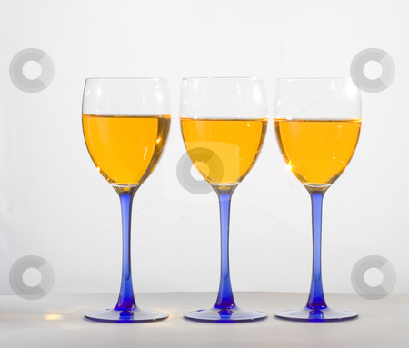 Wine glasses in a row stock photo, Three wine glasses filled with liquid by Matt Baker