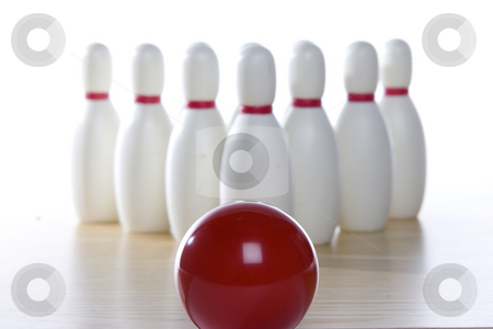 Bowling ball and pins stock photo, A bowling ball is lined up at the pins. Focus is on the ball in the foreground. by Matt Baker