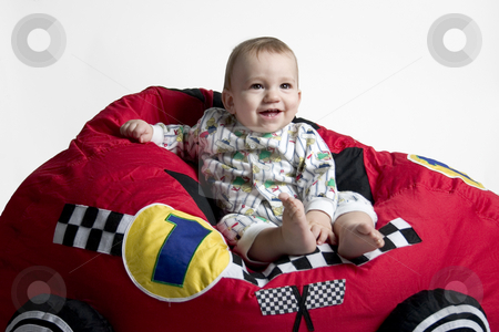 Sitting on a car stock photo, A baby sits on a toy car by Matt Baker