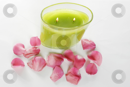 Candle and rose petals stock photo, A candle sits lit next to several rose petals by Matt Baker