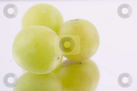 Three grapes stock photo, Three delicious grapes isolated on a mirror by Matt Baker