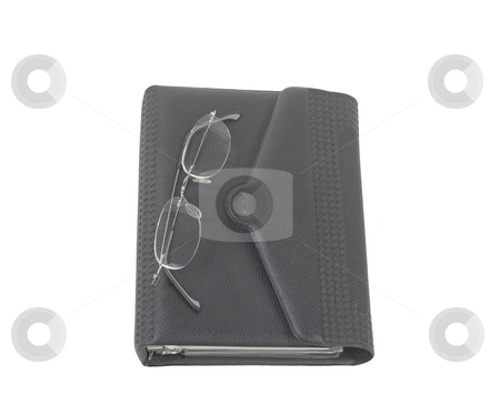 Daily planner with glasses stock photo, A pait of glasses sits on a daily planner by Matt Baker