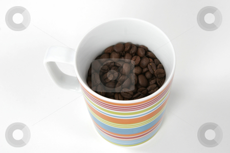 Coffee mug and beans stock photo, A coffee mug sits full of beans by Matt Baker