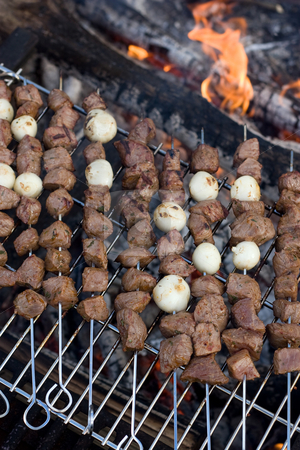 Shish Kebabs stock photo, Beef shish kebab skewers cooking over a hot camp fire. by Todd Arena
