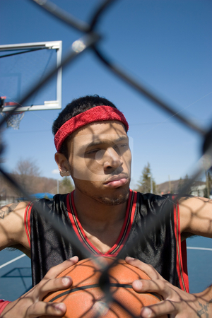 Basketball Player stock photo, A young basketball player gripping the ball tightly. by Todd Arena