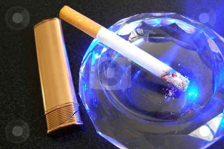 Cigarette and lighter stock photo, Cigarette in ashtray and lighter on the black table by Sergej Razvodovskij