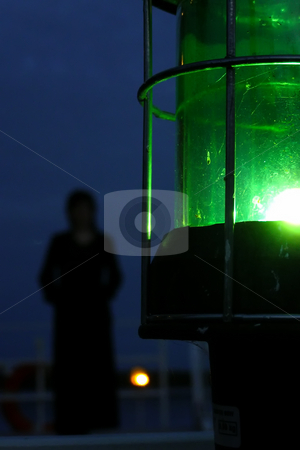 Illusion of halloween stock photo, Silhouette of woman on a nightly deck with a green lantern on a foreground by Sergej Razvodovskij