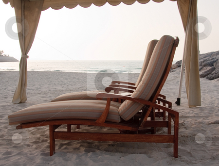 Pair of sun loungers on beach stock photo, Two sun loungers underneath a shaded tent on a sandy beach by the ocean by Steven Heap