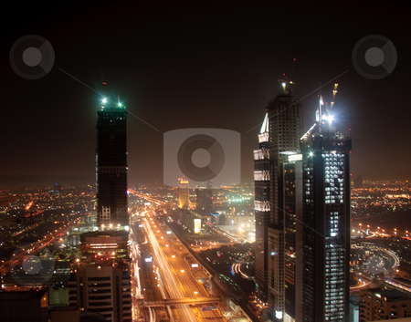 Cityscape of Dubai stock photo, Towering city skyscraper blocks in Dubai at night by Steven Heap