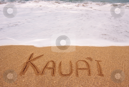 The word Kauai written into the sand in front of surging tide stock photo, White foam of the tide coming towards the name Kauai scratched in the sand by Steven Heap