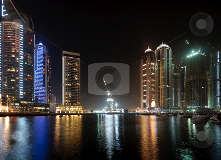 Marina in Dubai at night stock photo, Modern skyscrapers reflected in the marina in Dubai with a contruction underway in the center by Steven Heap