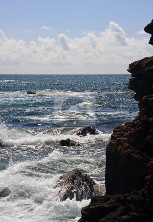 Rocky headland and raging ocean stock photo, Backlit view of the raging ocean with a red craggy rock face on right by Steven Heap